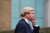 English: A barrister on a mobile phone outside Southwark Crown Court.