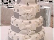 A contemporary white wedding cake decorated with sugar bows.