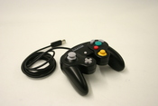 English: black nintendo game cube кг:Чёрный контроллер Nintendo GameCube.