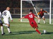 Association football (soccer), Bloomington, Indiana, 1996, by Rick Dikeman. The offensive player (in red) has sprinted past two defenders (in white) and is about to shoot the ball at the goal or pass it across the field to a teammate in front of the goal.