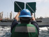 USS Mitscher Sailor signals to USNS Leroy Grumman during a connected replenishment