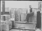 This black and white photo shows a tally clerk sitting with a truck load of beer cases. These cases were the first consignment of liquor following the lifting of Prohibition in the (then) Federal Capital Territory.