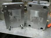 English: Standard two plate injection molding tool. Cavity and Core are insert in the mold base. The cavity and core are spark eroded into the shape that is required. Two plates - The two blocks you see. Five cavities - There are five cavities that will m