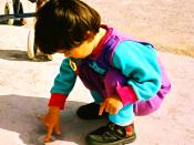 Young child playing at ease in a squatting position