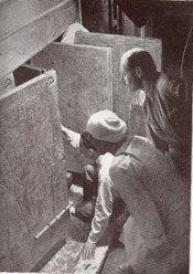 English: Howard Carter (kneeling), an Egyptian workman, and Arthur Callender at doors of burial shrines in Pharao Tutankhamen's tomb. Magyar: Howard Carter (térdel), egy egyiptomi munkás és Arthur Callender Tutanhamon fáraó sírjának kinyitása pillanatában