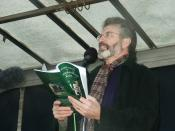 Gerry Adams at the Fermanagh Commemoration, reading aloud into a microphone.