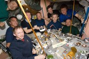 The crews of STS-127 and Expedition 20 enjoy a meal inside Unity.