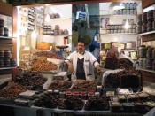 Date seller in the old souq in Kuwait City, surrounded by dates from Kuwait, Iran, Saudi Arabia and elsewhere.