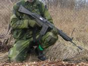 Soldier demonstrating gun safety by keeping the fingers off the trigger and the weapon pointed in a safe direction even while it is safetied.