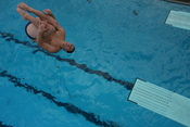English: A male diver performs a reverse dive from the 3 meter springboard in the tuck position