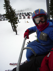 Chair lift restraining bar holding a happy 6-year-old passenger. This is the Bruno lift at Timberline Lodge ski area