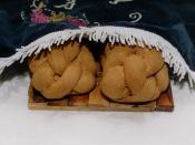 Two braided Shabbat challahs placed under an embroidered challah cover at the start of the Shabbat meal