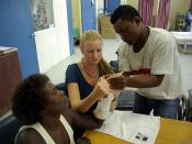 Occupational Therapist Melanie Glapa works with student George Hage to assist hand therapy patient 'Pemoli' at the physiotherapy ward at the National Referral Hospital, Honiara.
