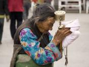 Tibet: An elderly Tibetan women holding a prayer wheel on the Lhasa's pilgrimage circuit of Barkhor. The Barkhor, a quadrangle of streets that surrounds the Jokhang Temple, is both the spiritual heart of the holy city and the main commercial district for