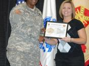 English: Col. Lillian Dixon, garrison commander, presents Hope Stephens, human resources assistant with the Directorate of Human Resources, with a certificate during the Employee of the Month award presentation Tuesday at the Solomon Center. Stephens was