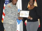English: Col. Lillian Dixon, garrison commander, presents Melody Porter, human resources assistant with the Directorate of Human Resources, with a certificate during the Employee of the Month award presentation Tuesday at the Solomon Center. Porter was on