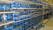 English: Bottled water fills an aisle in a supermarket