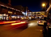 Cannery Row at Night. Dusk over the city of Monterey on Cannery Row (formerly Ocean Ave.) as cars pass by while City police investigate a vehicle blocking a hotel entrance. On the street in front of the south end of, 652 Cannery Row, Monterey, CA 93940.