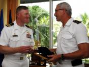 US Navy 090527-N-4047W-264 Cmdr. John Wade, commanding officer of the guided-missile destroyer USS Preble (DDG 88), left, exchanges gifts with Rear Adm. Jean Louis Vichot