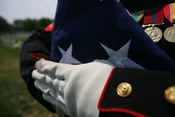English: A folded American flag held by a United States Marine at the funeral of Douglas A. Zembiec.