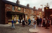 Tourists are show round the set of the ITV soap opera Coronation Street, viewing the Rovers Return Inn at Granada Studios, Manchester, England.
