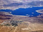 Lake Mead. Boulder City with its two golf courses and airport, is in the foreground. Hoover Dam is on the right.