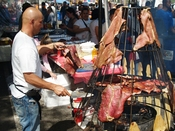 English: Spit barbecue meat hanging on Avenue C in the East Village (Loisaida section) during a street fair