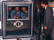 The crew of Apollo 11 in quarantine after returning to Earth, visited by Richard Nixon.