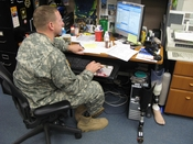 English: Major David Rozelle works at his desk next to his extra prosthesis. He keeps them there so he can switch them out, depending on his activity. He uses one to run, one to bike and one with a boot with his uniform. As deputy to the program manager f