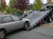 English: A car being loaded onto a flatbed tow truck
