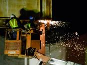 English: Workman cutting a old footbridge with Oxy-acetylene welding torch.