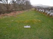 English: The Cout of Keilder's Grave This low grass mound is labelled as the Cout of Keilder's Grave, traditionally the grave of a Tynedale Baron who terrorised these lands util he was drowned in the nearby Hermitage Water. Stands alongside Hermitage Chap
