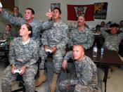 """English: Pros vs. GI Joes Army Spc. Meghan Phillips, Spc. Cody Black, Staff Sgt. James Wagner, Spc. Liam Walsh and Pfc. Eric Liesse (kneeling) of the Joint Task Force Public Affairs Office play a game of """"Halo 3"""" against Green Bay Packers players Mike Mon"""