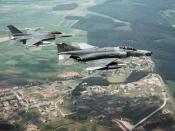 A U.S. Air Force McDonnell Douglas F-4G Phantom II Wild Weasel aircraft, foreground, and a General Dynamics F-16C Fighting Falcon aircraft of the 23rd Tactical Fighter Squadron, both assigned 52nd Tactical Fighter Wing, fly over Spangdahlem Air Base.