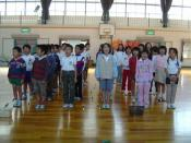 Students singing in a gym at a Japanese elementary school.