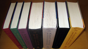 All seven books in the Harry Potter series in order without their dust jackets. Each hardcover book used a different two-color scheme. The books are the first American editions published by Scholastic. Author's collection.