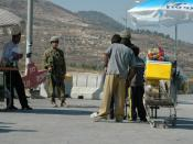 An Israeli soldier buys from Palestinian children selling drinks near a checkpoint