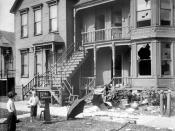 English: a house with broken windows and debris in the front yard during a race riot in Chicago, Illinois. Two young white boys are standing in front of the house and looking at it.