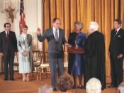 English: Justice William Rehnquist is sworn in as Chief Justice by his predecessor, Warren Burger as Judge and Mrs. Antonin Scalia and President Ronald Reagan look on.