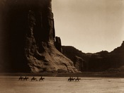 English: E. S. Curtis (1904): Canon de Chelly – Navajo. Seven riders on horseback and dog trek against background of canyon cliffs. Français : E. S. Curtis (1904). Canyon De Chelly. Sept cavaliers et un chien cheminent sur fond des falaises du canyon.