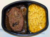 A modern TV dinner with Salisbury steak and macaroni and cheese.