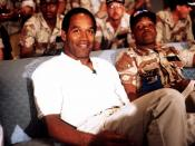 NBC Sports commentator and former professional football player O. J. Simpson sits with a group of servicemen to watch a Thanksgiving Day football game. Simpson is visiting U.S. troops who are in the region for Operation Desert Shield.