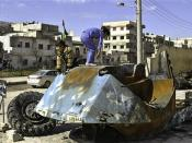 Syrian girls play on top of a destroyed Syrian riot police tank at Bayada neighborhood in Homs Syria