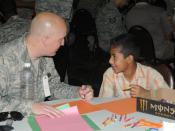 English: Air Force Tech. Sgt. Josh A. Sallee, the logistics civil augmentation program requirements manager for the 332nd Expeditionary Civil Engineer Squadron, and a Lake Geneva, Wis., native, colors with the child he is mentoring Oct. 10 at Iraqi Kids'