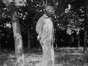 A man lynched from a tree. Face partially concealed by angle and headgear.