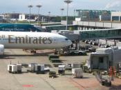 View of the ground handling services of Singapore Changi Airport, servicing an Emirates Boeing 777-300 (A6-EMO), with a Cathay Pacific