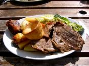 A Sunday roast consisting of roast beef, roast potatoes, vegetables, and yorkshire pudding