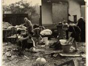 Siege of Warsaw by German forces in September of 1939. A Polish family performs their daily chores amidst the remnants of their household furnishings that they have reassembled outside the charred ruins of their home in Warsaw.