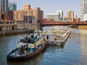 A tugboat pushing a barge westward along the main stem of the Chicago River