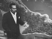 English: Cuban dictator Fulgencio Batista in March 1957, standing next to a map of the Sierra Maestra mountains where Fidel Castro's rebels were held up.